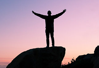 A silhouette of a man holding out his arms in praise on a rock